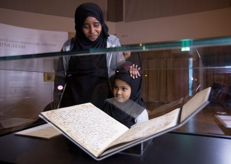 A Muslim woman and her daughter look at the replica of the manuscript on display.