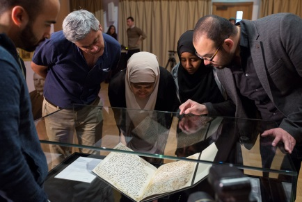 A group of people look at the replica of the manuscript on display inside a glass case.
