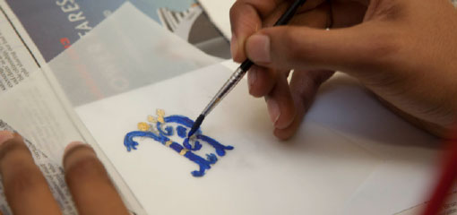 Student working on illuminating a letter in the style of Byzantine manuscript decoration.