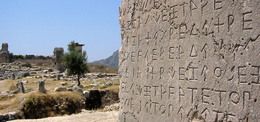 Photo of the xanthian obelisk in the ruined lycian city of xanthos turkey, with the harpy towers in the back ground