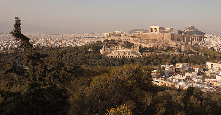 Photograph across the cityscape of Athens with the ruins of the Acropolis in the background