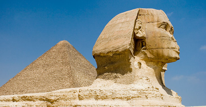 Photograph of the sphynx with a pyramid in the background