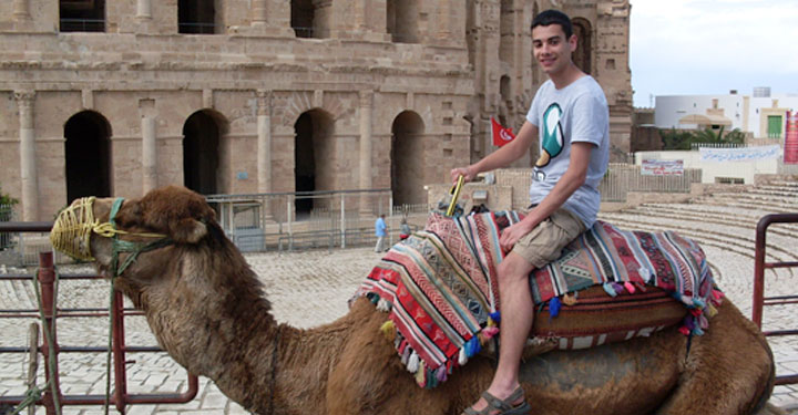Photo of CAHA alumnus Mark Desai (BA in Archaeology and Ancient History, 2014) astride a camel