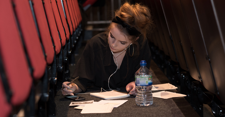 Student writing in theatre, Photo by Patricia Crummay © RSC