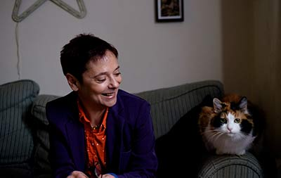 Lisa Gee sat on a couch with a cat beside her