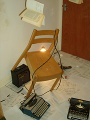 Photograph of a chair, typewriters, books and papers disorientated