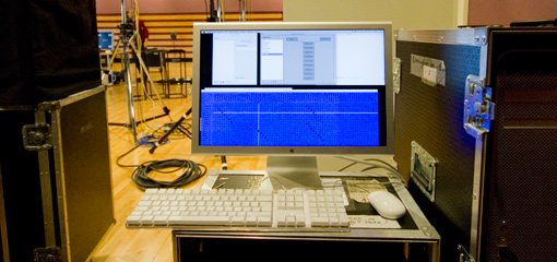 Photograph of a mac with audio software in a performance space