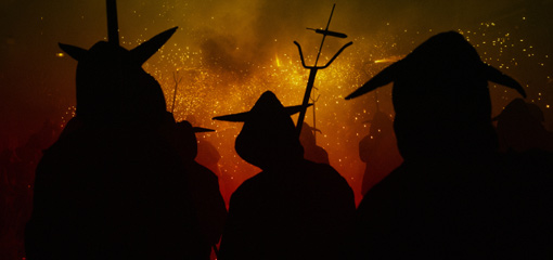 Photograph of silhouetted figures ina torchlit procession