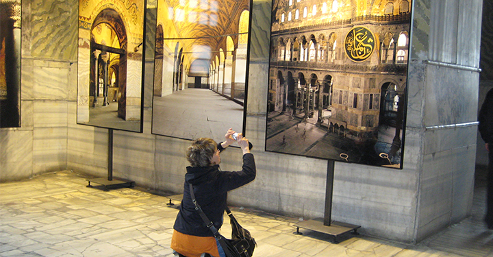 a lady taking a picture of a photographic display at the hagia sophia in istanbul, turkey
