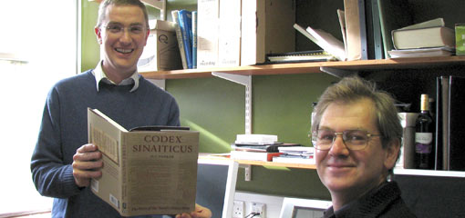 Photograph of two lecturers, one seated and one holding a publication on Codex Sinaiticus