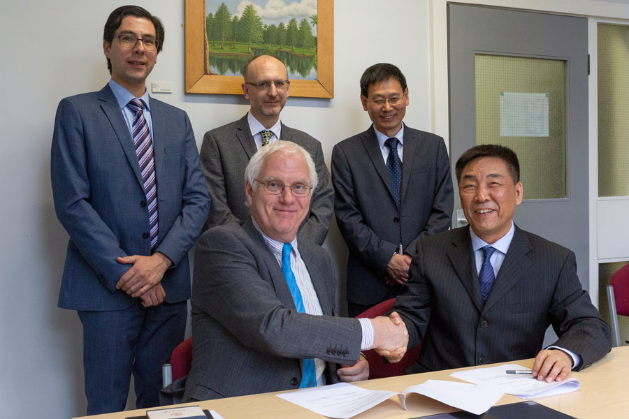 Professor Jianping Wang, Dean of the School of Foreign Languages of Renmin University of China, and Professor Michael Whitby, Head of the College of Arts & Law at the University of Birmingham signing the Memorandum of Understanding, with (left to right) D