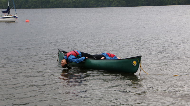Two students balancing on a canoe