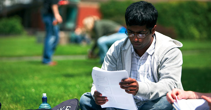 Student studying lecture notes on the grass on campus