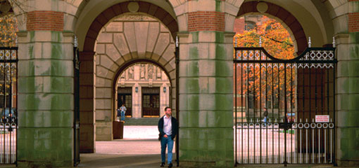 Picture of a student standing in front of the University of Birmingham and Law School Arches