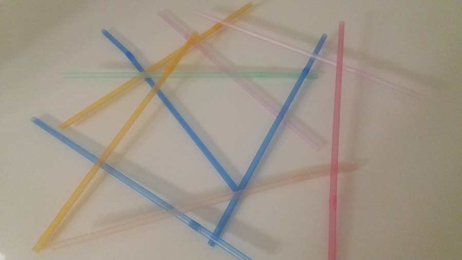 Coloured straws scattered on a table, overlapping each other