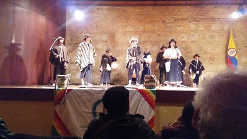 A photograph of a musical performance given by Paez people. There is a group of musicians dressed in indigenous clothing playing instruments.