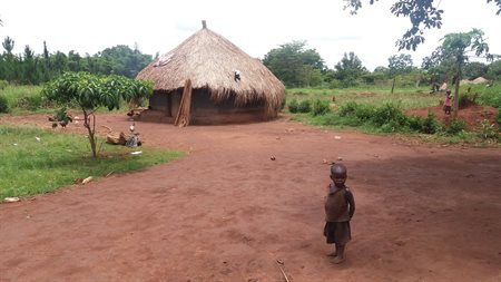 A photograph a small Ugandan property, which is a mud hut with a thatched roof. A small Ugandan boy stands outside.