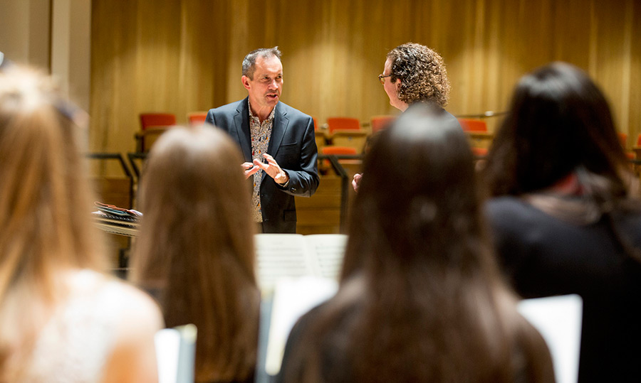 Composer Jonathan Dove speaking to Alexander Creamer and the University Women's Choir in rehearsal