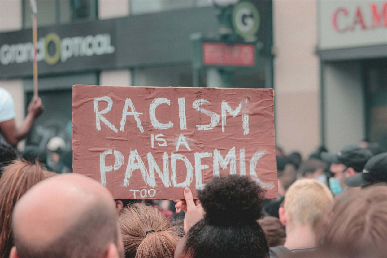 Protest sign that says 'Racism is a pandemic too'