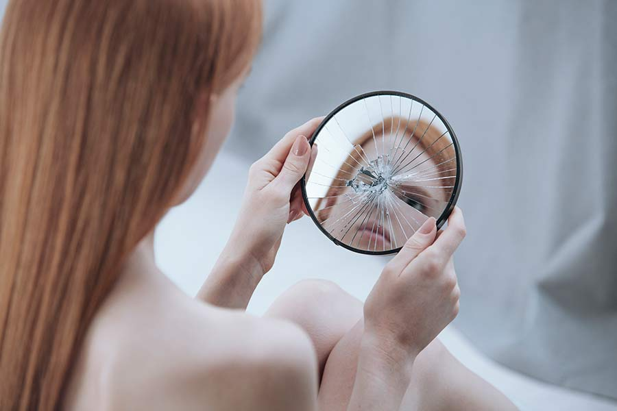 A woman looking at her reflection in a cracked hand mirror