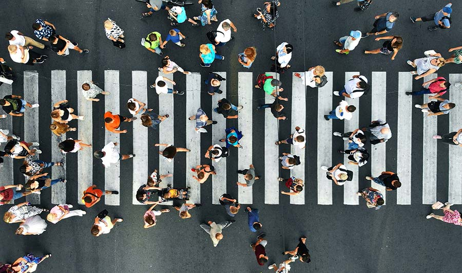 Aerial view of a pedestrian crossing with lots of people walking on it