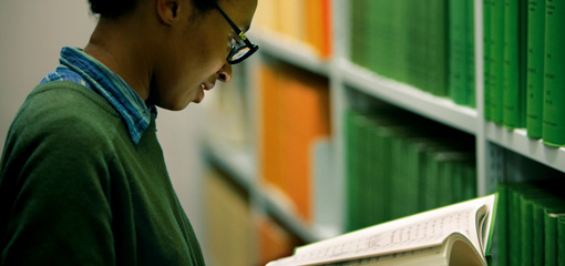 Photograph of a student at a shelf in the library