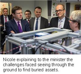 Nicole explaining to the minister the challenges faced seeing through the ground to find buried assets