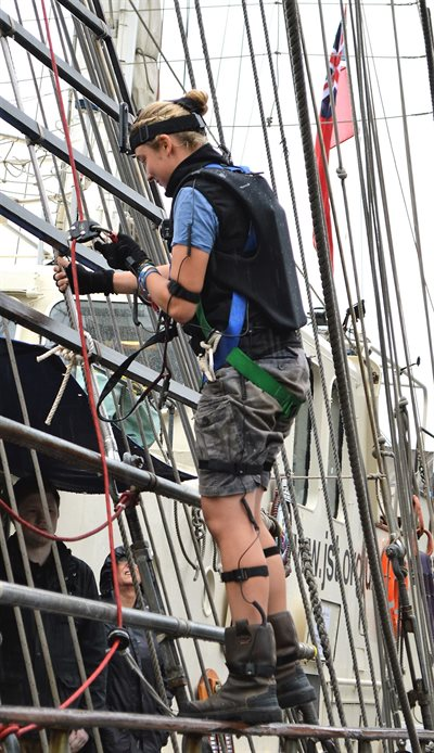 Beth Goss scaling Lord Nelson tall ship wearing motion capture suit