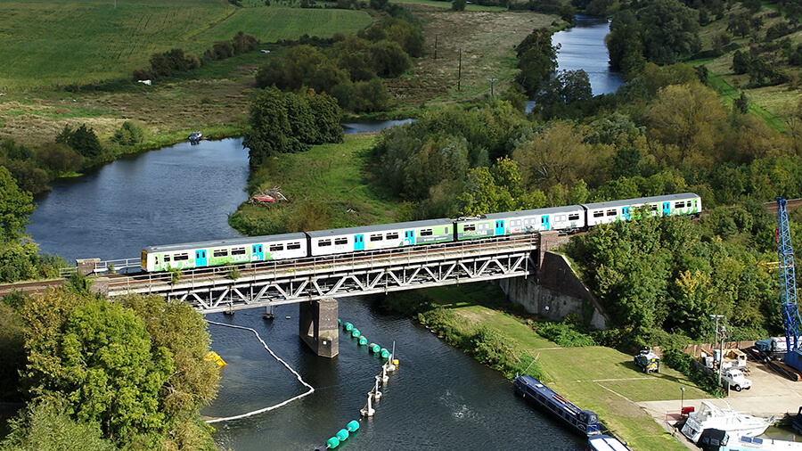 Drone shot of hydroflex hydrogen-powered train crossing a railway bridge