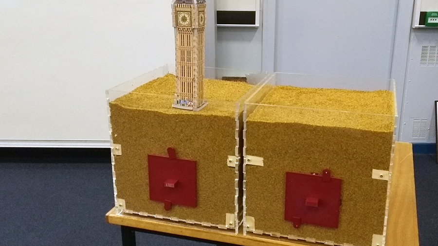 Model of Big Ben clock tower sitting in box of sand. Next to it is another box of sand without a tunnelling shield. The equipment was used to demonstrate how tunnelling shields prevent tunnels collapsing