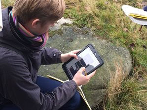 Student looking at a tablet in the field