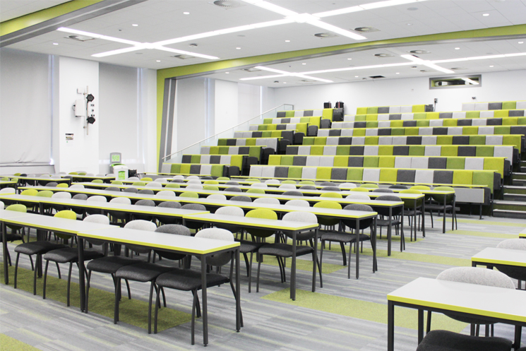 Image of a lecture theatre with green and grey seats and a two rows of grey tables