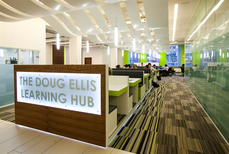 Image of The Doug Ellis Learning Hub with tables and students studying