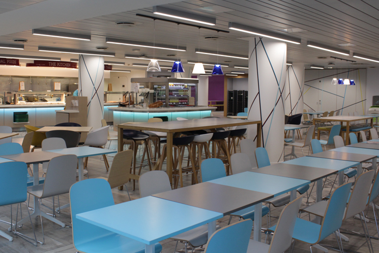 Image of a cafeteria with chairs, tables and a food counter at the back