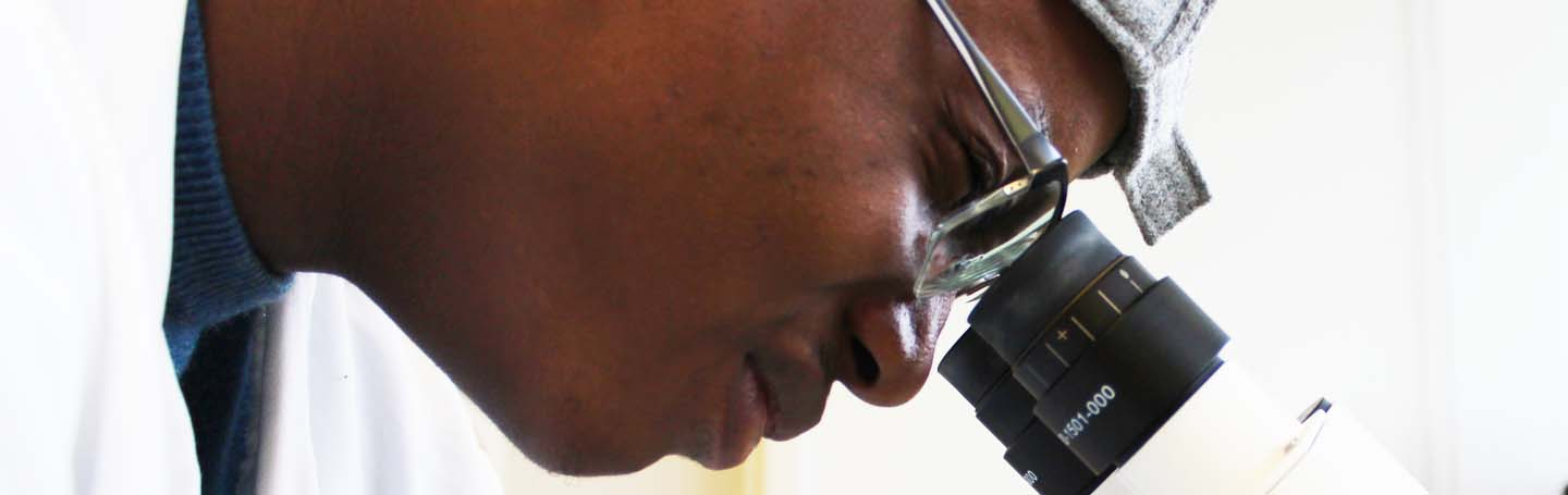 male looking through a microscope