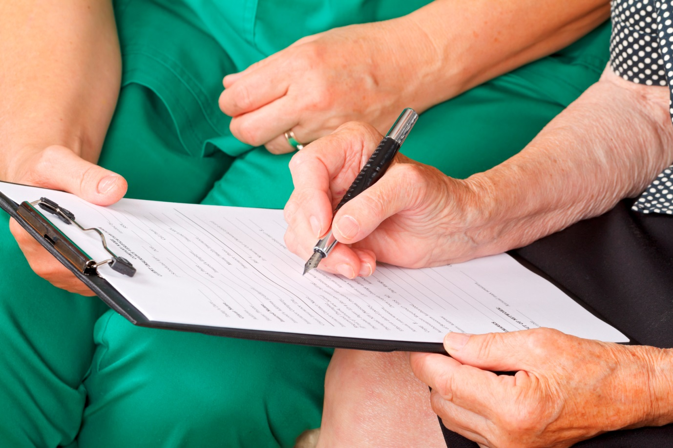 elderly patient completing a form with healthcare worker
