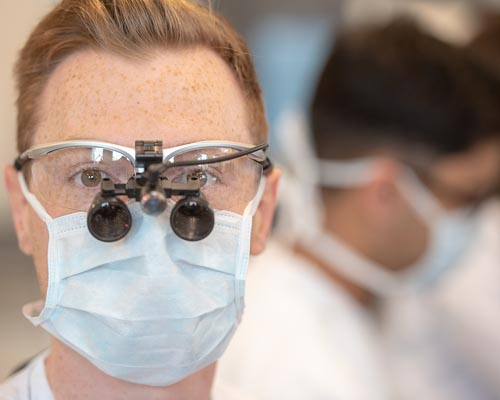 Male dental student wearing facemask and magnifying glasses