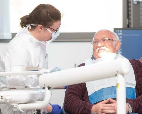 Female dental student talking to a male patient