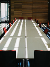 A photo of an empty meeting desk and chairs, with shadows on the table