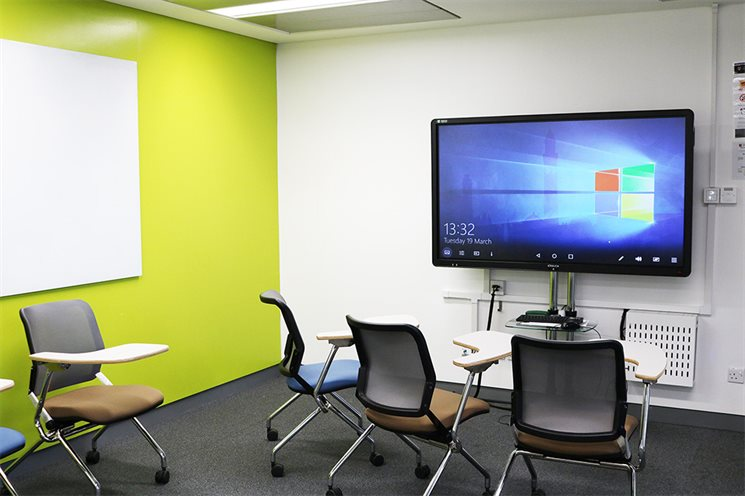 Image of room with computers, screen and whiteboard