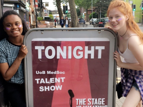 "Two students by a sign that reads ""Tonight, UoB MedSoc Talent Show"""