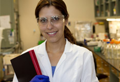 Female lab scientist holding a textbook within a laboratory