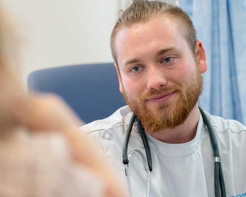 Male nursing student speaking to patient which is out of shot