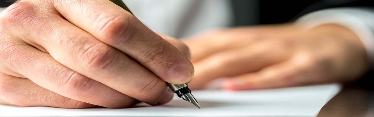 Man signing paper with green fountain pen