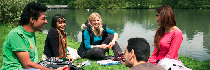 students sitting by lake