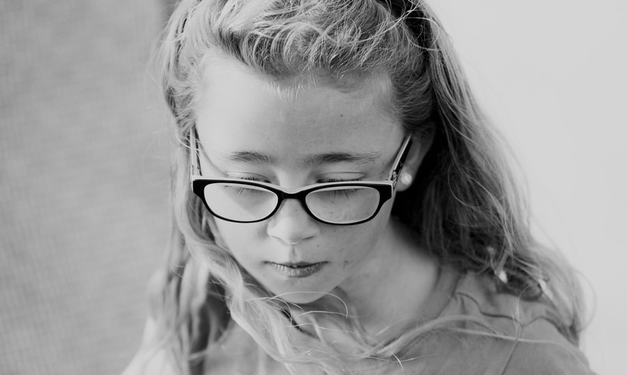 Black and white photograph of a young girl in glasses
