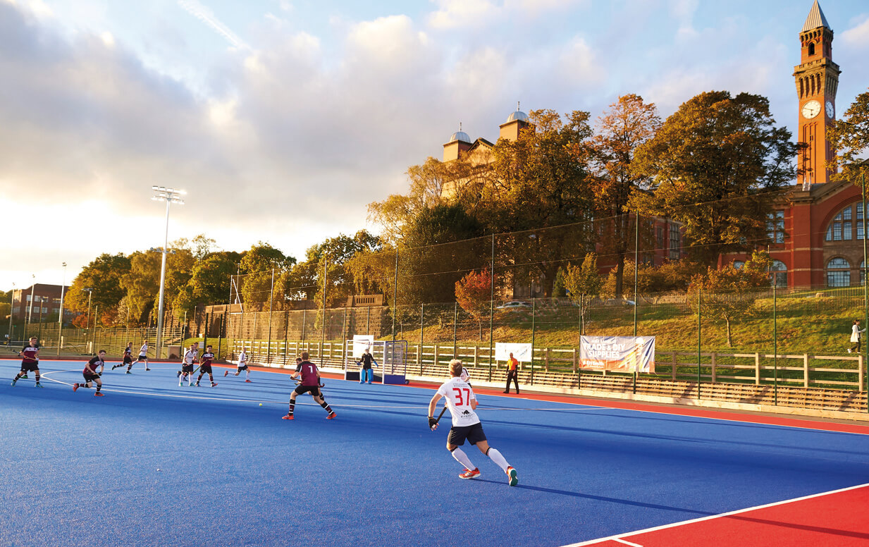 Hockey match taking place on the University of Birmingham's Metchley Lane synthetic pitches, with 'Old Joe' clocktower in the background.