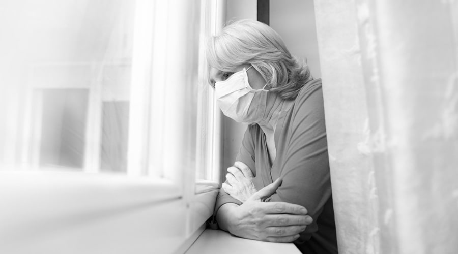 Sad senior woman looking out of her window with a face mask on