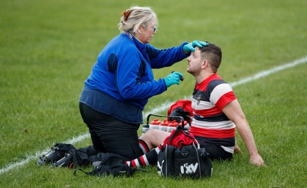 Rugby player being attended to by a medical practitioner
