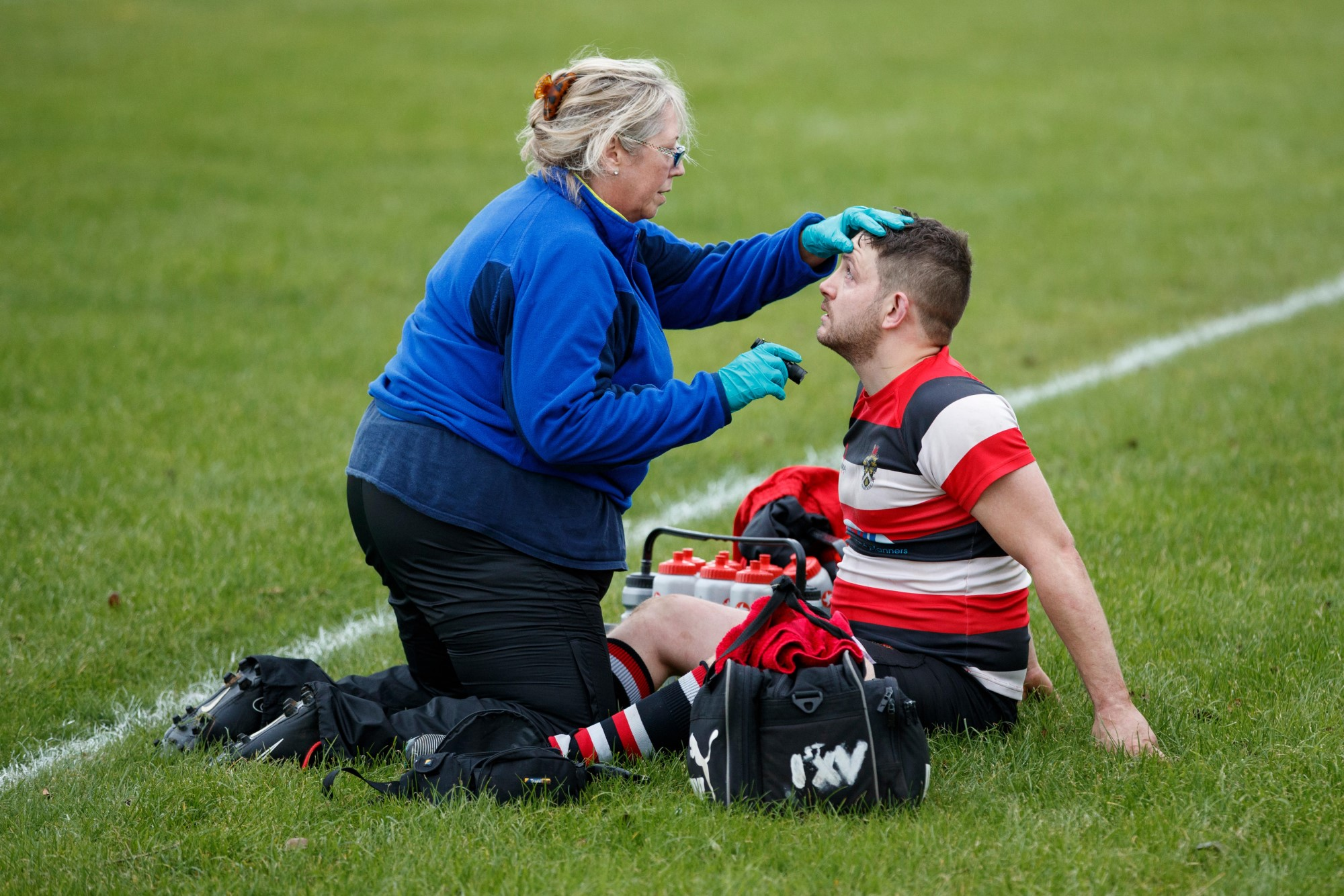 A rugby player being checked by a medic after a knock to the head